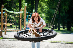 Woman swinging her dog Stock Images