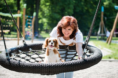 Woman swinging her dog Royalty Free Stock Photos