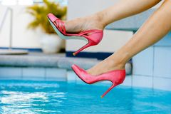Woman Swinging Her Foot Above Pool Water royalty free stock images