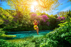 Woman swinging on the river. Happy young woman swinging with bungee above the river in the forest stock photography