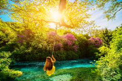 Woman swinging on the river. Happy young woman swinging with bungee above the river in the forest stock photo