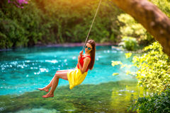 Woman swinging on the river. Happy young woman swinging with bungee above the river in the forest stock images