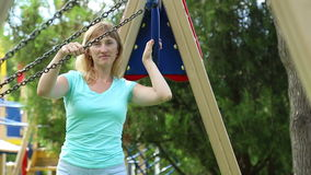 Woman swinging on a swing of her children stock video