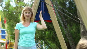 Woman swinging on a swing of her children stock video footage