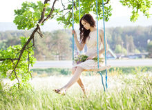 Woman is swinging on a swing in summer forest. Stock Photo