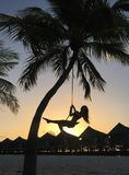 Woman swinging at the tropical beach royalty free stock images