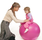 The woman swings the child on fitball Royalty Free Stock Image