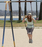 A Woman Swings in a Park by a Bay Royalty Free Stock Photo