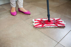 Woman swiping the kitchen floor Royalty Free Stock Images