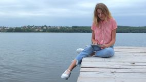 Woman swiping at tablet while sitting near lake in slow motion stock video