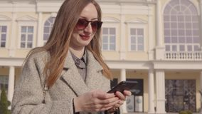 Woman is swiping on touch screen of smartphone, reading sms and viewing photos stock video