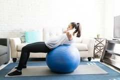 Woman on swiss ball doing abs exercise. Side view of fit young latin woman doing abs exercise on swiss ball in living room Stock Photos