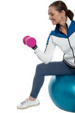 Woman on swiss ball working out with dumbbells Stock Images
