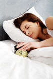 Woman switches off alarm clock. Royalty Free Stock Photo