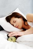 Woman switches off alarm clock. Stock Image