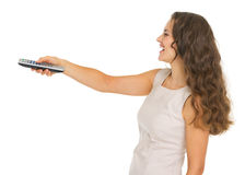 Woman switching channels with tv remote control. Happy young woman switching channels with tv remote control royalty free stock image