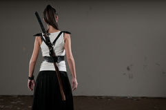 Woman With Sword. Beautiful woman with her back towards the camera and katana on her back Stock Photo