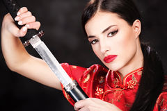 Woman with sword. Pretty woman holding katana weapon Stock Photo