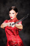 Woman with sword. Beautiful girl dressed in a kimono with katana in her hands Royalty Free Stock Images