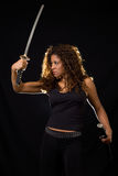 Woman with a sword. Attractive Hispanic woman wearing all black holding a samurai sword standing on black Royalty Free Stock Photo