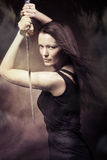Woman with sword. Studio portrait of a young woman with a samurai sword Royalty Free Stock Image