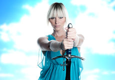 Woman with sword and cross. Fantasy woman with sword and cross in blue dress royalty free stock photo