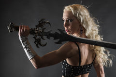 Woman and sword. Performer woman wearing sexy costume and holding a sword, grey smoky background Royalty Free Stock Images
