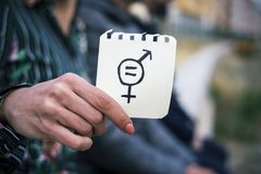 Woman with a symbol for gender equality. Closeup of a young woman outdoors showing a piece of paper in front of her with a symbol for gender equality drawn in it royalty free stock photo