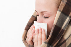 A woman with a symptoms cold. Flu allergy wiping or blowing her nose Stock Photos