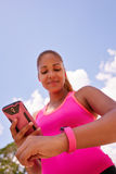 Woman Syncronizes Fitness Watch Fitwatch With Phone Stock Photos