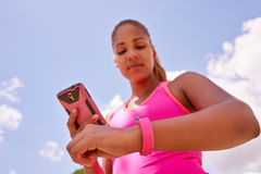 Woman Syncronizing Fitness Watch Fitwatch With Phone Stock Photos
