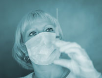 Woman with a syringe in mask. Stock Photo
