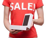Woman with t-shirt with an inscription sale in hand smartphone mobile phone shop buy discount. On a white background isolation Stock Images
