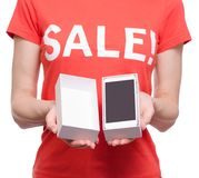Woman with t-shirt with an inscription sale in hand smartphone mobile phone shop buy discount. On a white background isolation Royalty Free Stock Photo