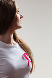 Woman in t-shirt with pink cancer ribbon on gray Royalty Free Stock Photos