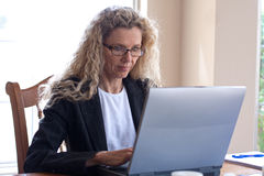 Woman on table with laptop Royalty Free Stock Photos