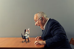 Woman on the table and mad screaming man. Small businesswoman on the table and mad screaming man Royalty Free Stock Image
