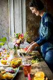 Woman table setting fruits and drinks for party Stock Photography