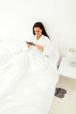 Woman tablet bed Royalty Free Stock Photos