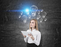 Woman with tablet and blue light bulb sketches Stock Images