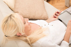 Woman with tablet and cherry on the sofa Royalty Free Stock Image
