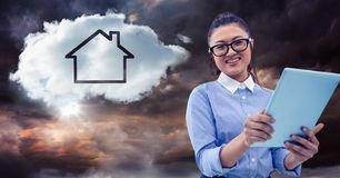 Woman with tablet and cloud with house against stormy sky Stock Images