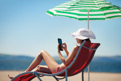 Woman with tablet computer in deck chair Stock Photos