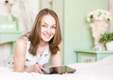 Woman with tablet computer on her bed Stock Photos