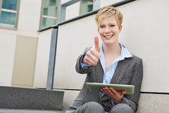 Woman with tablet computer holding thumbs up Stock Images