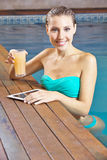 Woman with tablet computer in pool Royalty Free Stock Image