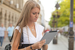 Woman with tablet computer walking on street Royalty Free Stock Image