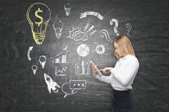 Woman with tablet computer and yellow dollar light bulb Royalty Free Stock Image