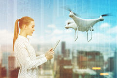 Woman with a tablet, drone, city toned Royalty Free Stock Image