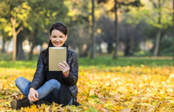 Woman with a Tablet in a Forest in the Autumn. Portrait of a young happy smilling woman with a tablet sitting in a yellow autumn forest Stock Image
